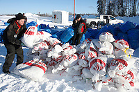 Volunteer load handlers stack musher's food bags bound for Swentna at the Willow airport during the first day of flying straw, musher's dog food bags and people food & gear out to checkpoints south of the Alaska Range.  Saturday Feb. 21, 2009  Iditarod 2009