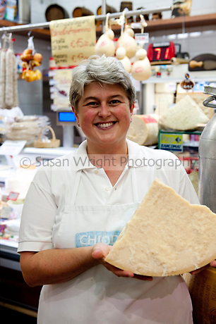 Vanna Sala, in her family's market stall at Mercato Albinelli in Modena.  Her family's Formaggeria has been at the Mercato Albinelli since 1958 when her father Ivo Sala owned the stall.  Vanna is holding a piece of Parmigiano Reggiano of Modena.