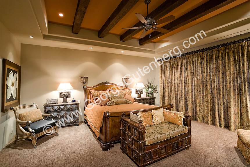 Luxurious master bedroom with beautiful draperies, fireplace and furnishings Stock photo of bedroom