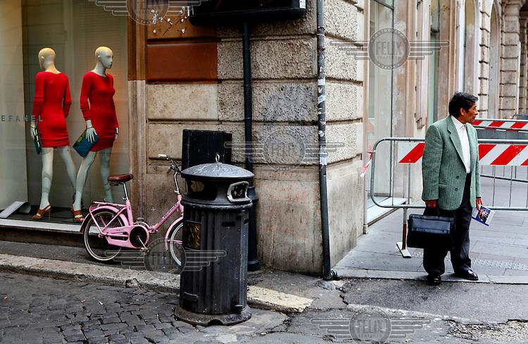 A man waits outside a clothing shop near the Spanish Steps.