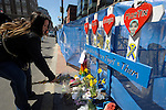 (Boston Ma 042014) Debbie Schmitz, 40, of Chicago, takes a moment to remember the deceased victims by adds flowers to a small memorial next to the finish line on Boylston Street in Boston Sunday, April 20, 2014, the day before the Boston Marathon. (Jim Michaud Photo) For Sunday