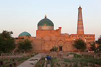 General view of Pahlavan Mahmud Mausoleum, 14th-16th century, Khiva, Uzbekistan, pictured at sunset. Visible are its blue tile-covered dome which commands Khiva's skyline and on the right the Islam Hodja minaret, 1910. Commissioned by the reforming Grand Visier, Islam Khodja, the minaret is 44.8 metres high, tapering towards the top, its ochre brick alternating with bands of decorative blue and white tiles. It is the final architectural achievement of the Khanates. Khiva, ancient and remote, is the most intact Silk Road city. Ichan Kala, its old town, was the first site in Uzbekistan to become a World Heritage Site(1991). Picture by Manuel Cohen.