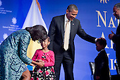 United States President Barack Obama and First Lady Michelle Obama greet four-year-olds Piper Shillingford and Ajani Joseph Grant, from Stuyvesant Heights Montessori Academy in Brooklyn, New York at the groundbreaking ceremony of the Smithsonian National Museum of African American History and Culture in Washington, D.C. on Wednesday, February 22, 2012. Lonnie Bunch, director of the museum, is pictured at far right.  The museum is scheduled to open in 2015 and will be the only national museum devoted exclusively to the documentation of African American life, art, history and culture..Credit: Andrew Harrer / Pool via CNP