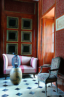 An antique tapestry chair, a Chinese urn and a wicker lantern in a corner of this living room are just some of the eclectic objects to be found in every room of the chateau