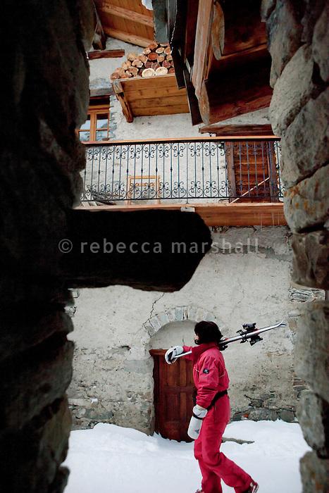 A woman walks down a village street in Bonneval sur Arc, Savoie, France, 16 February 2012.