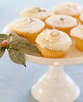 Fairy cakes with generous icing served on a cake stand with sugared leaves as decorations