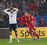 Gareth Bale celebrates the winning goal for Wales as Jamie Mackie stands gutted