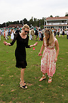 Young women tread in divots during break in play. The Guards Polo Club, Windsor Great Park. England.