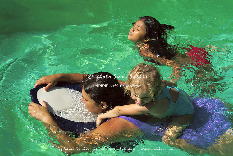 Woman piggybacking a little girl in a swimming pool for Chicken in swimming pool