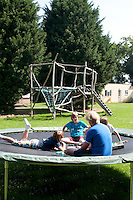 """Philipp Klaus, holding an English class on the trampoline using the """"Upwords"""" game, Summerhill School, Leiston, Suffolk. The school was founded by A.S.Neill in 1921 and is run on democratic lines with each person, adult or child, having an equal say.  You don't have to go to lessons if you don't want to but could play all day.  It gets above average GCSE exam results."""