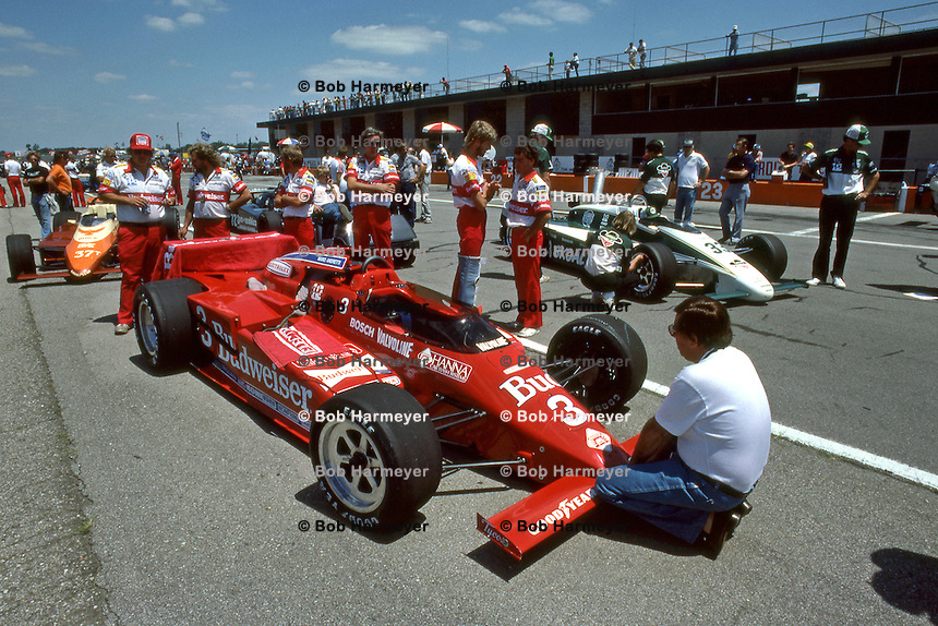 BROOKLYN, MI - JULY 22: Carl Haas, on the pre-race starting grid, kneels at the front of the Lola T800/Cosworth driven to victory by Mario Andretti in the Michigan 500 CART IndyCar race at Michigan International Speedway near Brooklyn, Michigan, on July 22, 1984.
