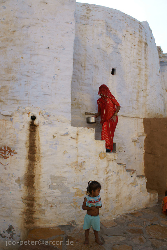 street scene with woman in red sari climbing stairs and child in Fort Jaisalmer, Rajastan, India
