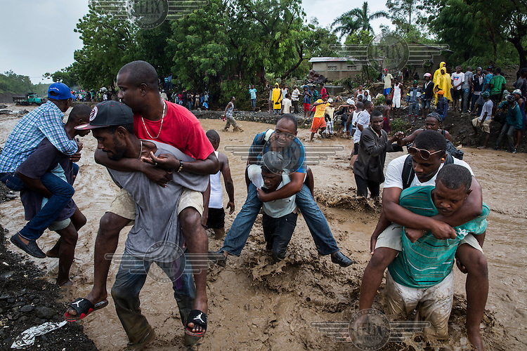 People are carried over La Digue River. Following the collapse, during Hurricane Matthew, of a bridge people were forced to wade across the water course. The downfall of the bridge meant emergency responders where unable to reach the worst hit southwestern peninsula of the island. Hurricane Matthew, the first category 5 Atlantic hurricane since 2007, hit the island on 4 October 2016. Winds of up to 230km/h (145mph) tore across the worst affected areas, mainly in the south of the island, killing around over 1,000 people and leaving hundreds of thousands in need of assistance.