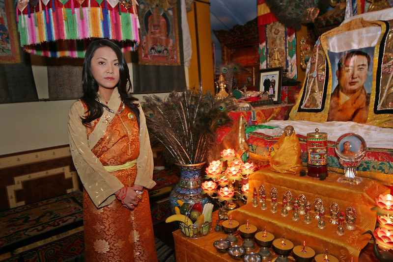 """BEIJING, CHINA - November 6, 2005 - The last Panchen Lama's daughter, Yabshi Pan Rinzinwangmo at her home in Beijing, standing next to a shrine dedicated to her late father. Yabshi Pan Rinzinwangmo is familiarly known to her friends as """"Renji"""" but to many others she is known as the """"Princess of Tibet"""". Her father was the 10th Panchen Lama, a Buddhist monk ranking close to the Dalai Lama in Tibet's spiritual leadership, who died in 1989. Her mother, Li Jie, is a former doctor in China's People's Liberation Army and granddaughter of a famous general in China's civil war. After 10 years studying in the United States, at high school in Los Angeles and then political science at the American University in Washington, Renji has just returned to China for further studies at the elite Tsinghua University to prepare for what she sees as her future role as a """"unifier""""."""