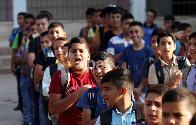 Palestinian schoolboys play exercises inside their school in the morning of the first day of the new year study, in the West Bank city of Nablus, on August 28, 2016. Photo by Nedal Eshtayah