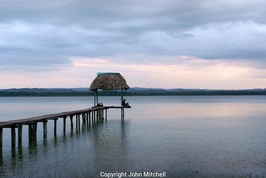 Person sitting on a wooden pier on Lake Peten Itza near  Flores, El Peten, Guatemala.