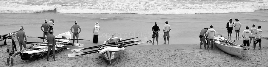 Surfboat crews watch the action as they wait for the start of their race at a surf carnival at Kurrawa on Queensland's Gold Coast.