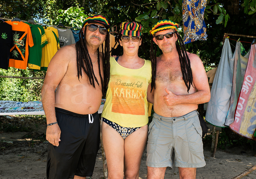 Tourist friends model dreadlock Jamaican hats on the beach, Negril, Jamaica