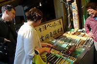 Tourists shopping for knifes, Tsukiji fish market, Tokyo, Japan, October 30 2009.