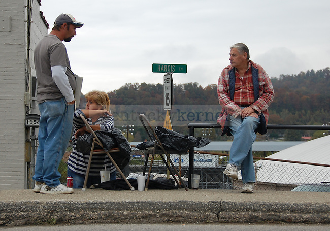 (from left) Ricky Robinson, Susan Miller and Bob Chapman watched as cars passed on Main Street in Jackson, Ky. on Thursday Oct. 13, 2011. Robinson was selling newspapers for 50 cents a piece to residents to Breathitt County. Photo by Brooke DiDonato