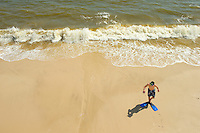 A teenage boy takes a break from swimming to relax on the beach on Dauphin Island, Alabama, a barrier island located three miles south of the mouth of Mobile Bay in the Gulf of Mexico. This island, which is approximately 14 miles long and less than two miles wide, appears to have fully recovered from the impact of Hurricane Katrina (2005) and the BP Deepwater Horizon Oil Spill in 2010. Both events greatly reduced tourism income (fewer people came to the island) and local business owners say many establishments went out of business. Today they say they're looking forward to a rebounding tourism business.