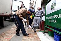 TUNJA-COLOMBIA, 16-04-2020: Un guarda de seguridad hace desinfección a los zapatos de una mujer al ingresar a un supermercado, durante la cuarentena total en el territorio colombiano causada por la pandemia  del Coronavirus, COVID-19. / A security guard disinfects a woman's shoes when entering a supermarket, during the total quarantine in the Colombian territory caused by the Coronavirus pandemic, COVID-19. / Photo: VizzorImage /Darlin Bejarano / Cont.