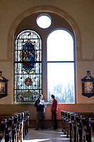 Two men read about the stained glass installed in one of the windows during an open house at the  new St. Paul's Catholic Church in Westerville.