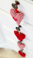 Small handmade hearts made from different fabrics hang from metal knobs on the kitchen drawers