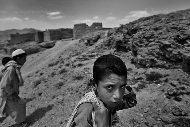 KHAK-E-JABAR DISTRICT, AFGHANISTAN - MAY 15. .Eight-year-old Zahedullah heads back to his village after a day of looking for scrap metal and shrapnel from exploded anti-personel mines outside his village in Khak-e-Jabar district. The areas in and around the capital Kabul were heavily mined during the Soviet invasion of Afghanistan during the 1980's. Many children such as Zahedullah collect shrapnel in order to sell as scrap metal - it is not uncommon that these children get maimed of killed by land mines they encounter while trying to make a living collecting scrap metal. (Javier Manzano / For The Washington Post). ..