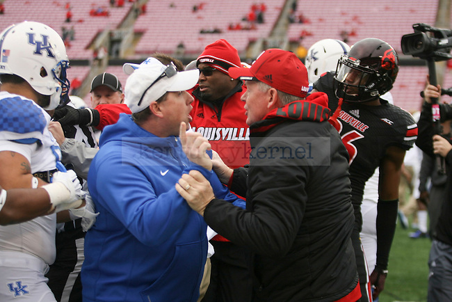Kentucky football assistant coach Dan Berezowitz and Louisville head coach Bobby Petrino scuffle on the field during warm ups at Papa John's Cardinal Stadium in Louisville, Ky., on Saturday, November 29, 2014. Photo by Michael Reaves | Staff