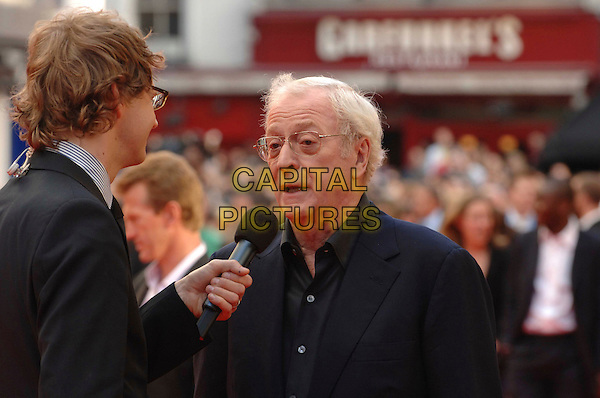 "SIR MICHAEL CAINE .Attending the UK Premiere for the new Batman movie ""The Dark Knight"", Odeon Leicester Square, London, England,.July 21st 2008..half length microphone being interviewed glasses .CAP/WIZ.©Wizard/Capital Pictures"