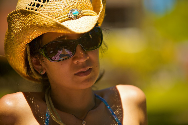 Clara during a summer day in Punta del Este, Uruguay. ..Woman wearing a cowboy hat and large size sun glasses, with her head slightly tilted with a pondering look.