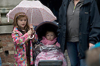 The Children's Parade which is the traditional  beginning of the Brighton Festival. A family watches the parade as rain threatens.