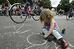 Two-year-old Bernadette Bulter draws in the street before the start of the 21st annual Summer Solstice Parade held Saturday, June 20, 2009 in Seattle, Wa. The parade was held Saturday, bringing out painted and naked bicyclists, bands, belly dancers and floats. (Jim Bryant Photo © 2009). .