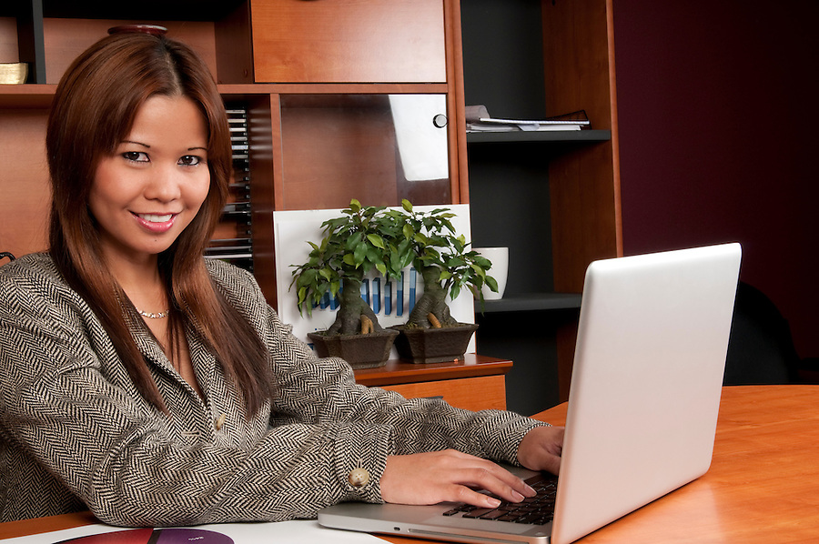 Young woman working in an office with laptop computer.