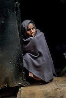 A lady at her house door step at a lane in Varanasi, Uttar Pradesh, India.