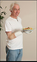 BNPS.co.uk (01202) 558833.Picture: Peter Willows..Chris can now enjoy previously impossible chores, like clearing dishes...Chris Taylor has become the first in the UK to be fitted with a bionic limb that has electronic fingers and thumb. Chris (58) from Ivybridge, Devon, lost his right hand when he fell off a jet-ski in 2009, but he has now been fitted with the £47,000 limb by specialists Dorset Orthopaedic.  Electrodes in the arm are able to sense muscle movements, and these signals are used to control electronic motors that move the fingers. Chris can now hold and grip a variety of different-sized objects, allowing him to carry out complex wiring work for his job as a service engineer.