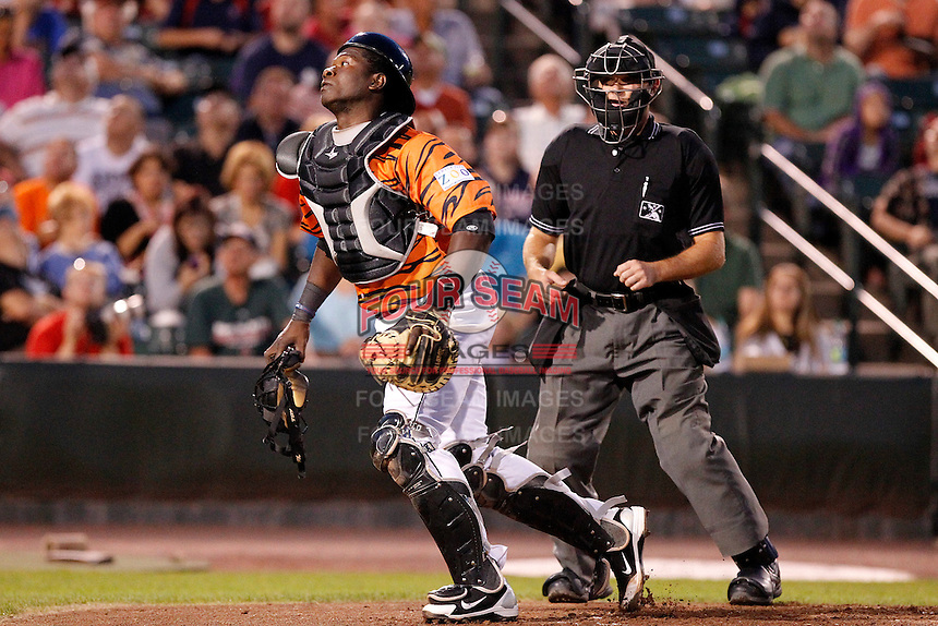 Rochester Red Wings catcher Jair Fernandez #48 chases down a foul ball as umpire Chris Ward looks on during a game against the Pawtucket Red Sox at Frontier Field on August 30, 2011 in Rochester, New York.  Rochester defeated Pawtucket 8-6 as the team wore special jerseys to be auctioned off after the game to benefit the zoo.  (Mike Janes/Four Seam Images)