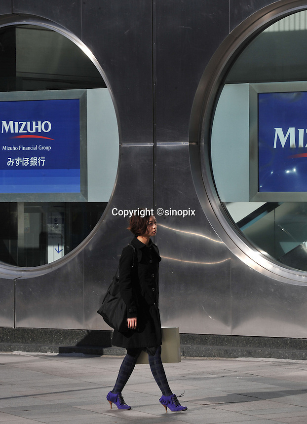 Locals pass Mizuho Bank in Tokyo, Japan. Mizuho Financial Group Inc., the Japanese bank with the biggest subprime writedowns in Asia, posted its second straight quarterly loss as the value of its stock slumped and bad loans rose. The company turned to a 145.1 billion yen ($1.6 billion) deficit in the three months ended Dec. 31 from a 66 billion yen profit a year earlier..