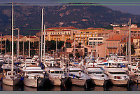 Mediterranean seaport scene, luxury yachts in port and hillside buildings, Corsica, France