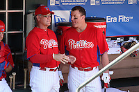 Philadelphia Phillies designated hitter Jim Thome #25 (right) talks with Ryne Sandberg #23 (left) in the dugout before a spring training game against the Houston Astros at Bright House Field on March 7, 2012 in Clearwater, Florida.  (Mike Janes/Four Seam Images)