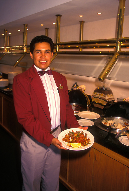 Waiter holding plate of food at buffet table at restaurant in Fiesta Inn Hotel, Leon, Guanajuato State, Mexico, North America