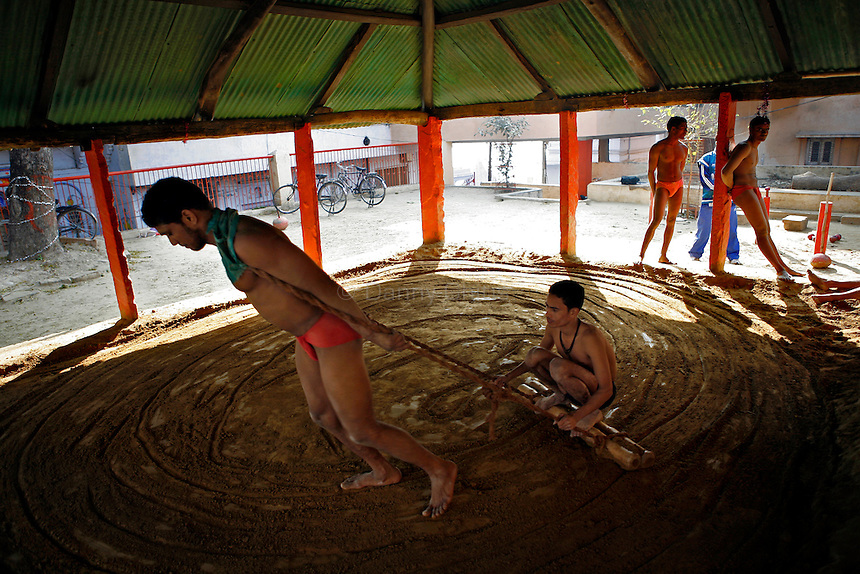 Wrestlers at an akhara near the Ganges river in Varanasi prepare the soil for a morning practice. The process itself is rigorous, where men take turn hauling each other on a plow. The ancient tradition of Indian wrestling, known as  kushti, thrives in Varanasi, one of the world's oldest cities. Wrestling gyms, or akhara, scattered around the city are of the few places where Hindu men from different casts are considered equals. Aside from bodybuilding, practiioners emphasize a life of discipline and celibacy. But as modernity sweeps India and Western sports like cricket become more popular, some akhara are being abandoned. While some prominent, government-run gyms switched to mats for Olympic-style wrestling, akhara in villages and towns maintain the old ways.