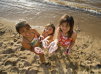Girls with shells on the beach in Haleiwa, North Shore of Oahu