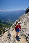Mountains and Female hiker hiking uphill on walking trail to the top of Moro Rock, Sequoia National Park, California