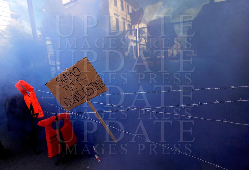 """Manifestazione davanti all'ambasciata turca per protestare contro gli accordi tra Unione Europea e Turchia sui migranti, a Roma, 1 maggio 2016.<br /> Smoke in front of the Turkish Embassy against the agreement between the EU and Turkey on migrants in Rome, 1 May 2016. The sign reads """"We are all illegals"""".<br /> UPDATE IMAGES PRESS/Riccardo De Luca"""