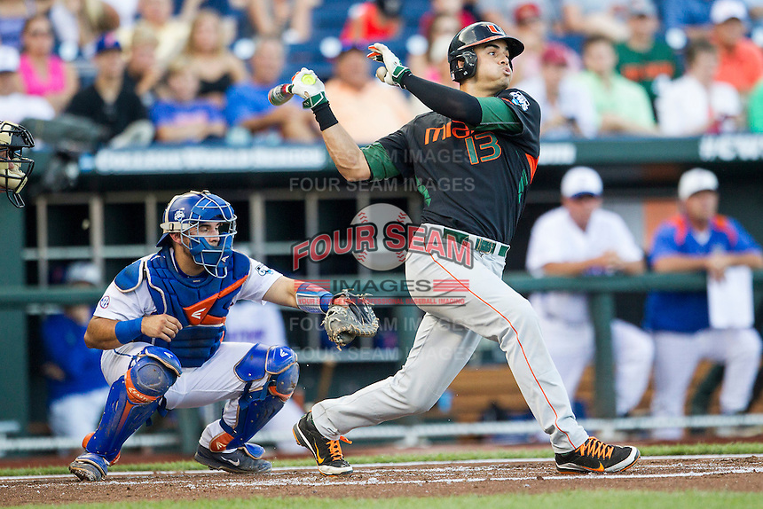 Miami Hurricanes outfielder Willie Abreu (13) follows through on his swing against the Florida Gators in the NCAA College World Series on June 13, 2015 at TD Ameritrade Park in Omaha, Nebraska. Florida defeated Miami 15-3. (Andrew Woolley/Four Seam Images)