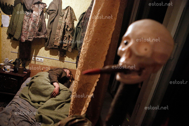 """UKRAINE, 02.2016, Novohrodivka, Oblast Donetsk. Ukrainian-Russian conflict concerning Eastern Ukraine / Foreign volunteers (""""Task Force Pluto"""") fighting with the far-right militia Pravyi Sektor against the Russian-backed separatists: Alex immediately falls asleep at the base after returning from a 7 days frontline duty, politely observed by a plastic skull with a bullet in its mouth. © Timo Vogt/EST&OST"""