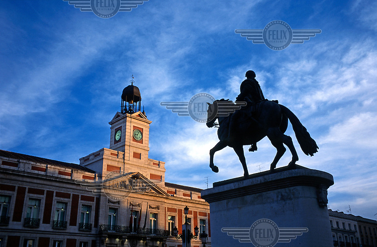 An equestrian statue of King Carlos III standing in the centre of Puerta del Sol (Gate of the Sun) in the heart of Madrid, with the regional government building illuminated by the setting sun..