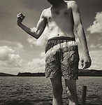 Vintage black and white print scan. 98-085-G #2. Brendan Works in swimming trunks making muscle at Moosehead Lake, ME.